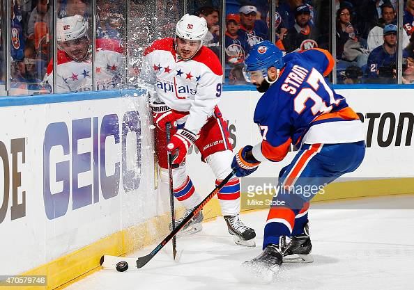 Marcus Johansson of the Washington Capitals battles for the puck with Brian Strait of the New York Islanders during Game Four of the Eastern...