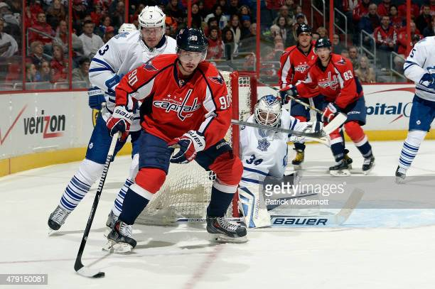 Marcus Johansson of the Washington Capitals brings the puck around the net against Dion Phaneuf of the Toronto Maple Leafs in the second period...