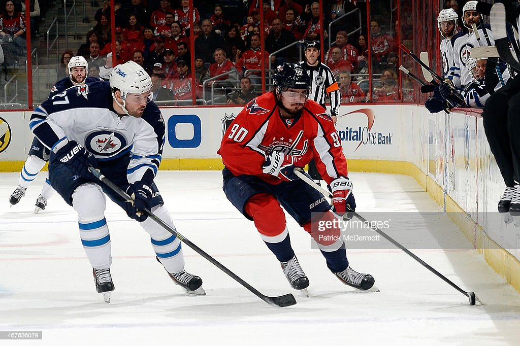Marcus Johansson #90 of the Washington Capitals controls the puck in the second period against Eric Tangradi #27 of the Winnipeg Jets during an NHL game at Verizon Center on February 6, 2014 in Washington, DC.