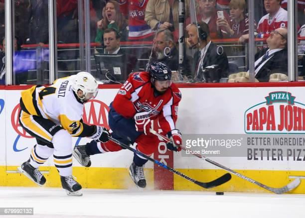 Marcus Johansson of the Washington Capitals is checked by Justin Schultz of the Pittsburgh Penguins in Game Five of the Eastern Conference Second...
