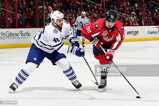 Marcus Johansson of the Washington Capitals moves the puck up ice against Roman Polak of the Toronto Maple Leafs in the second period during an NHL...