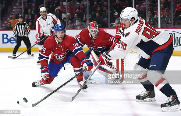Marcus Johansson of the Washington Capitals passes the puck against pressure from Jeff Petry the Montreal Canadiens in the NHL game at the Bell...