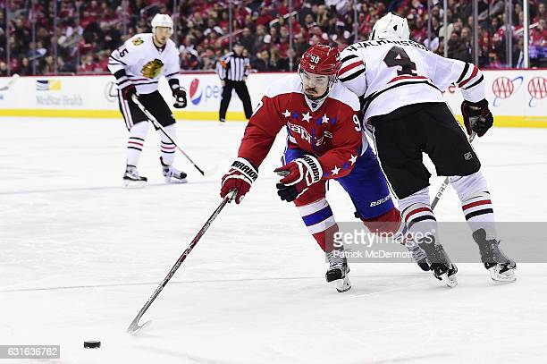 Marcus Johansson of the Washington Capitals skates after the puck past Niklas Hjalmarsson of the Chicago Blackhawks in the third period during an NHL...