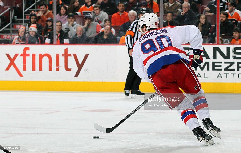 Marcus Johansson #90 of the Washington Capitals skates the puck against the Philadelphia Flyers on March 5, 2014 at the Wells Fargo Center in Philadelphia, Pennsylvania.