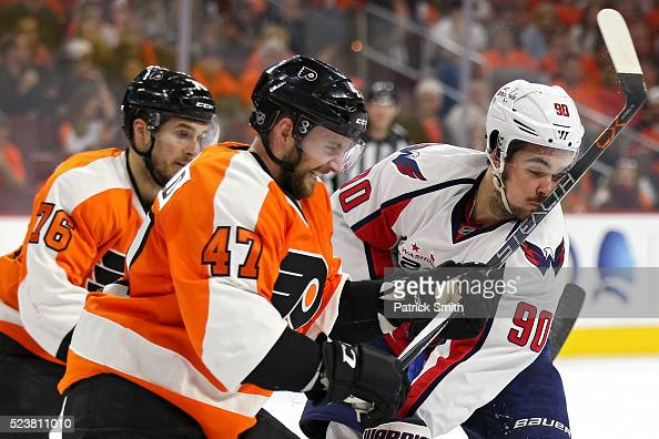Marcus Johansson of the Washington Capitals takes a highstick to the face from Andrew MacDonald of the Philadelphia Flyers during the first period in...