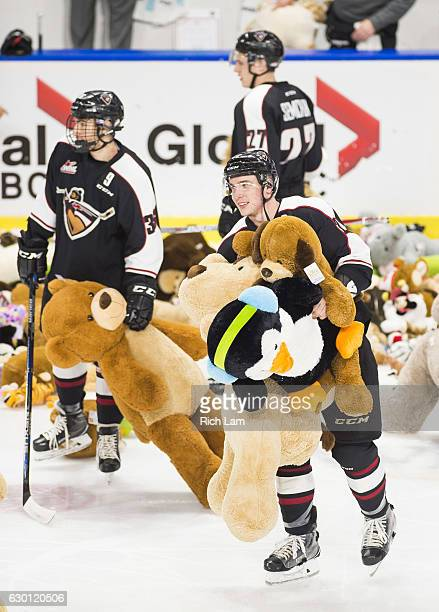 Marcus Kichton and Hunor Torzsok of the Vancouver Giants help pick up teddy bears thrown on the ice during the first period of their WHL game against...
