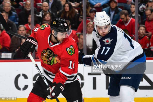 Marcus Kruger of the Chicago Blackhawks and Adam Lowry of the Winnipeg Jets watch for the puck in the first period at the United Center on January 26...