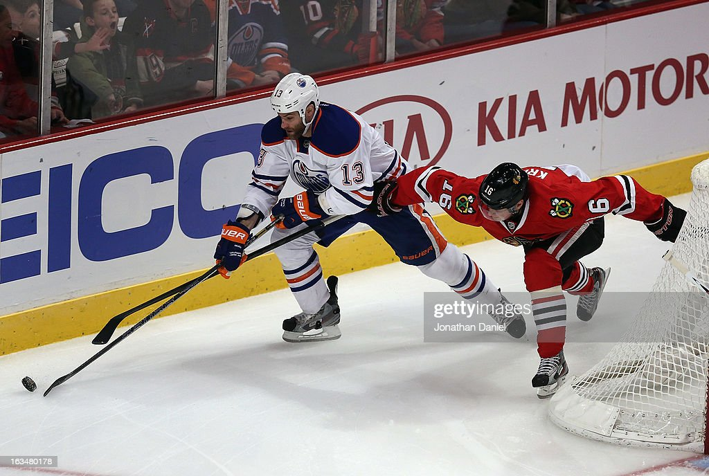 Marcus Kruger #16 of the Chicago Blackhawks and Mike Brown #13 of the Edmonton Oilers battle for the puck at the United Center on March 10, 2013 in Chicago, Illinois.