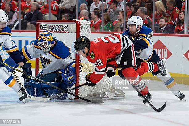 Marcus Kruger of the Chicago Blackhawks attempts to get the puck past goalie Brian Elliott of the St Louis Blues as Jaden Schwartz pushes behind in...
