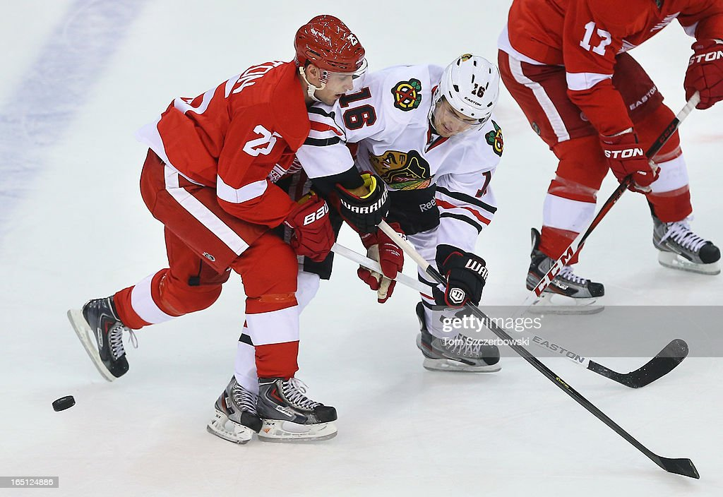 Marcus Kruger #16 of the Chicago Blackhawks battles for the puck during an NHL game against <a gi-track='captionPersonalityLinkClicked' href=/galleries/search?phrase=Cory+Emmerton&family=editorial&specificpeople=570505 ng-click='$event.stopPropagation()'>Cory Emmerton</a> #25 of the Detroit Red Wings at Joe Louis Arena on March 31, 2013 in Detroit, Michigan.