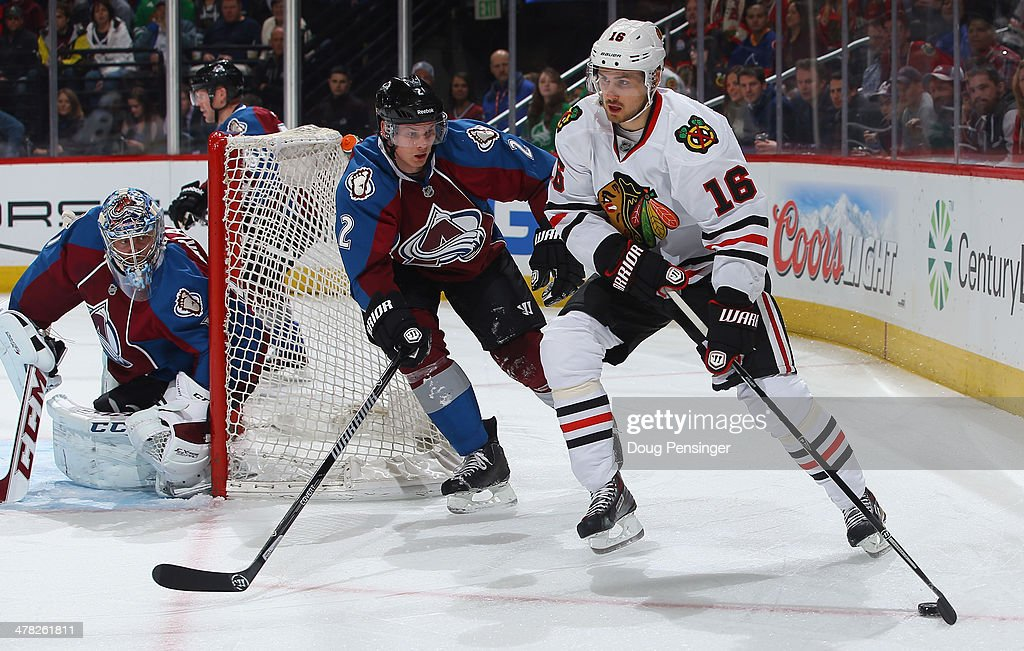 Marcus Kruger #16 of the Chicago Blackhawks controls the puck against Nick Holden #2 of the Colorado Avalanche as goalie Semyon Varlamov #1 of the Colorado Avalanche defends the goal at Pepsi Center on March 12, 2014 in Denver, Colorado.