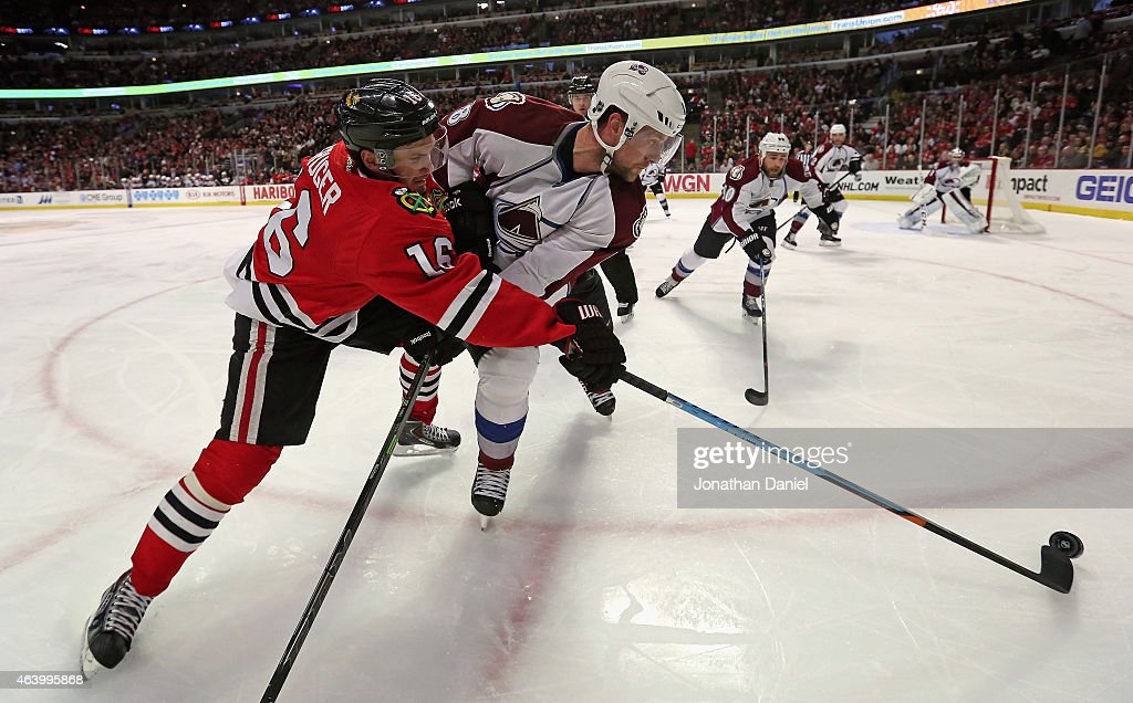 Marcus Kruger #16 of the Chicago Blackhawks knocks the puck away from <a gi-track='captionPersonalityLinkClicked' href=/galleries/search?phrase=Jan+Hejda&family=editorial&specificpeople=624333 ng-click='$event.stopPropagation()'>Jan Hejda</a> #8 of the Colorado Avalanche at the United Center on February 20, 2015 in Chicago, Illinois.