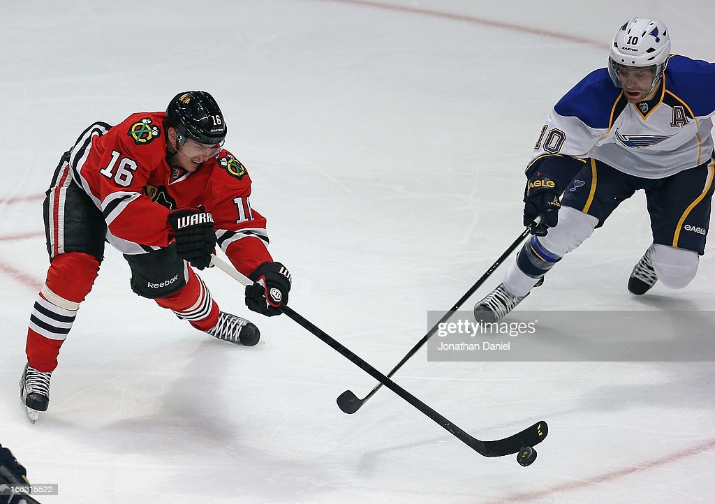 Marcus Kruger #16 of the Chicago Blackhawks knocks the puck away from Andy McDonald #10 of the St. Louis Blues at the United Center on April 4, 2013 in Chicago, Illinois. The Blues defeated the Blackhawks 4-3 in a shootout.