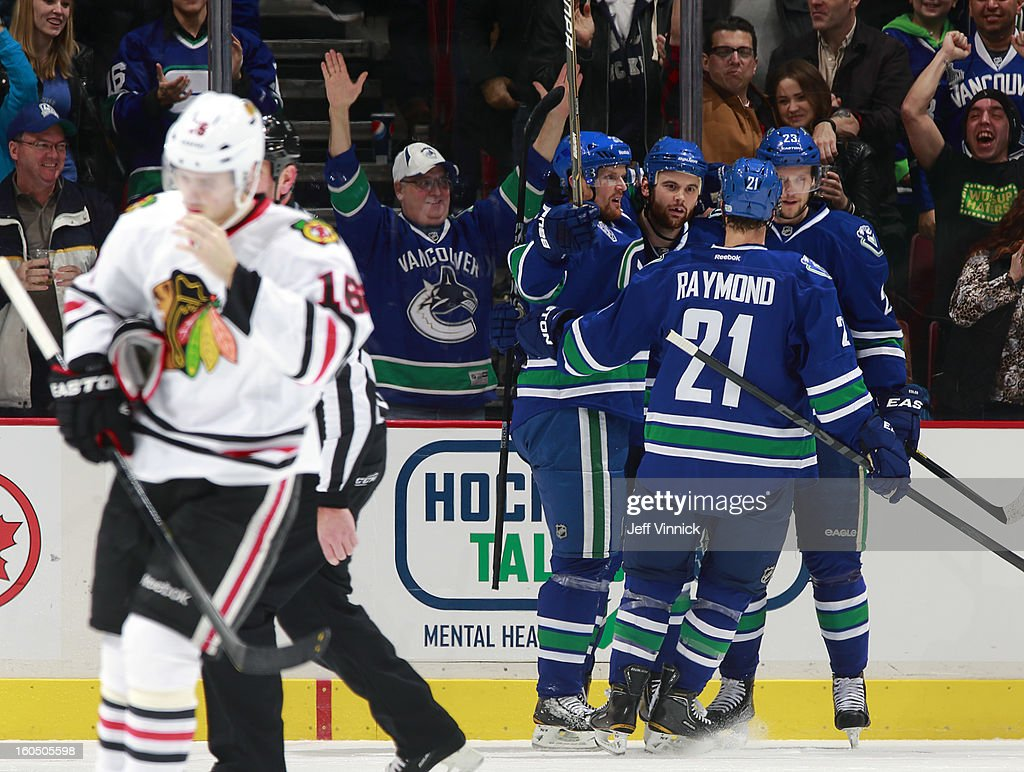 Marcus Kruger #16 of the Chicago Blackhawks skates away while Zack Kassian #9, Mason Raymond #21and Henrik Sedin #33 congratulate goal scorer Alexander Edler #23 of the Vancouver Canucks during their NHL game at Rogers Arena February 1, 2013 in Vancouver, British Columbia, Canada.