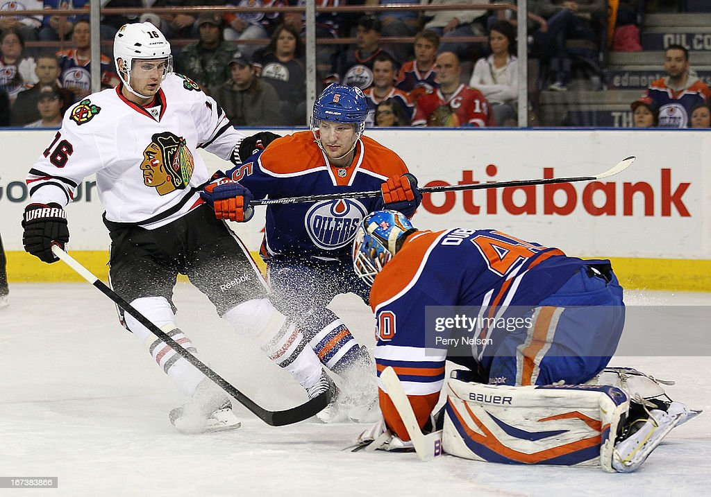 Marcus Kruger #16 of the3 Chicago Blackhawks drives the net while Ladislav Smid #5 defends and <a gi-track='captionPersonalityLinkClicked' href=/galleries/search?phrase=Devan+Dubnyk&family=editorial&specificpeople=2089794 ng-click='$event.stopPropagation()'>Devan Dubnyk</a> #40 of the Edmonton Oilers covers the puck at Rexall Place on April 24, 2013 in Edmonton, Canada.