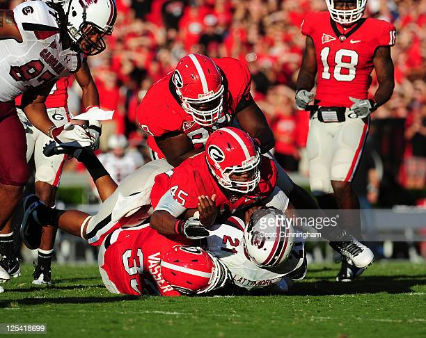 Marcus Lattimore of the South Carolina Gamecocks is tackled by Chase Vasser DeAngelo Tyson and Christian Robinson of the Georgia Bulldogs at Sanford...