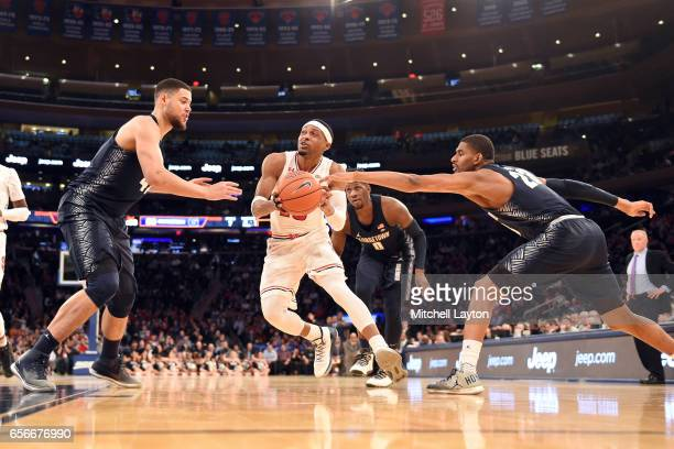 Marcus LoVett of the St John's Red Storm dribbles through Bradley Hayes and Rodney Pryor of the Georgetown Hoyas during the Big East Basketball...