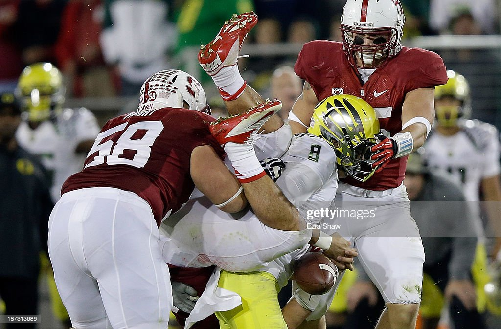 <a gi-track='captionPersonalityLinkClicked' href=/galleries/search?phrase=Marcus+Mariota&family=editorial&specificpeople=8572256 ng-click='$event.stopPropagation()'>Marcus Mariota</a> #8 of the Oregon Ducks fumbles the ball as he is tackled by David Parry #58, A.J. Tarpley #17 and Jarek Lancaster #35 of the Stanford Cardinal at Stanford Stadium on November 7, 2013 in Palo Alto, California.