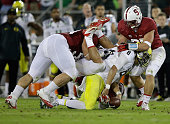 Marcus Mariota of the Oregon Ducks fumbles the ball as he is tackled by David Parry AJ Tarpley and Jarek Lancaster of the Stanford Cardinal at...