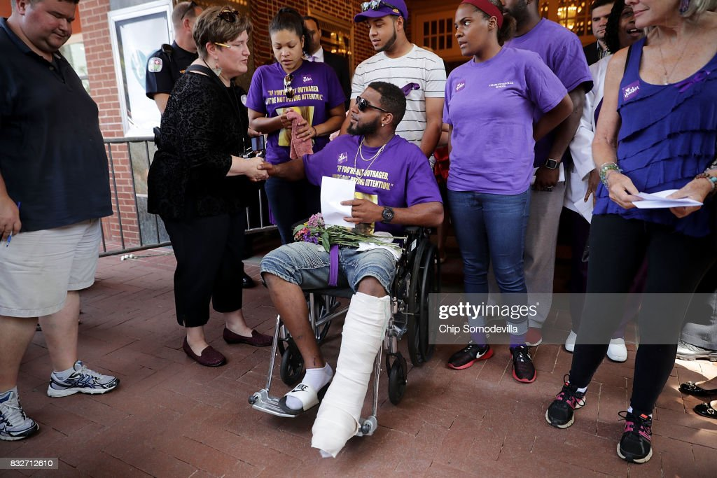 Marcus Martin (C), who was injured when a car plowed into a crowd of people protesting against the white supremacist Unite the Right rally, leaves the Paramount Theater following a memorial service for Heather Heyer August 16, 2017 in Charlottesville, Virginia. The memorial service was held four days after Heyer was killed when a participant in a white nationalist, neo-Nazi rally allegedly drove his car into the crowd of people demonstrating against the 'alt-right' gathering.
