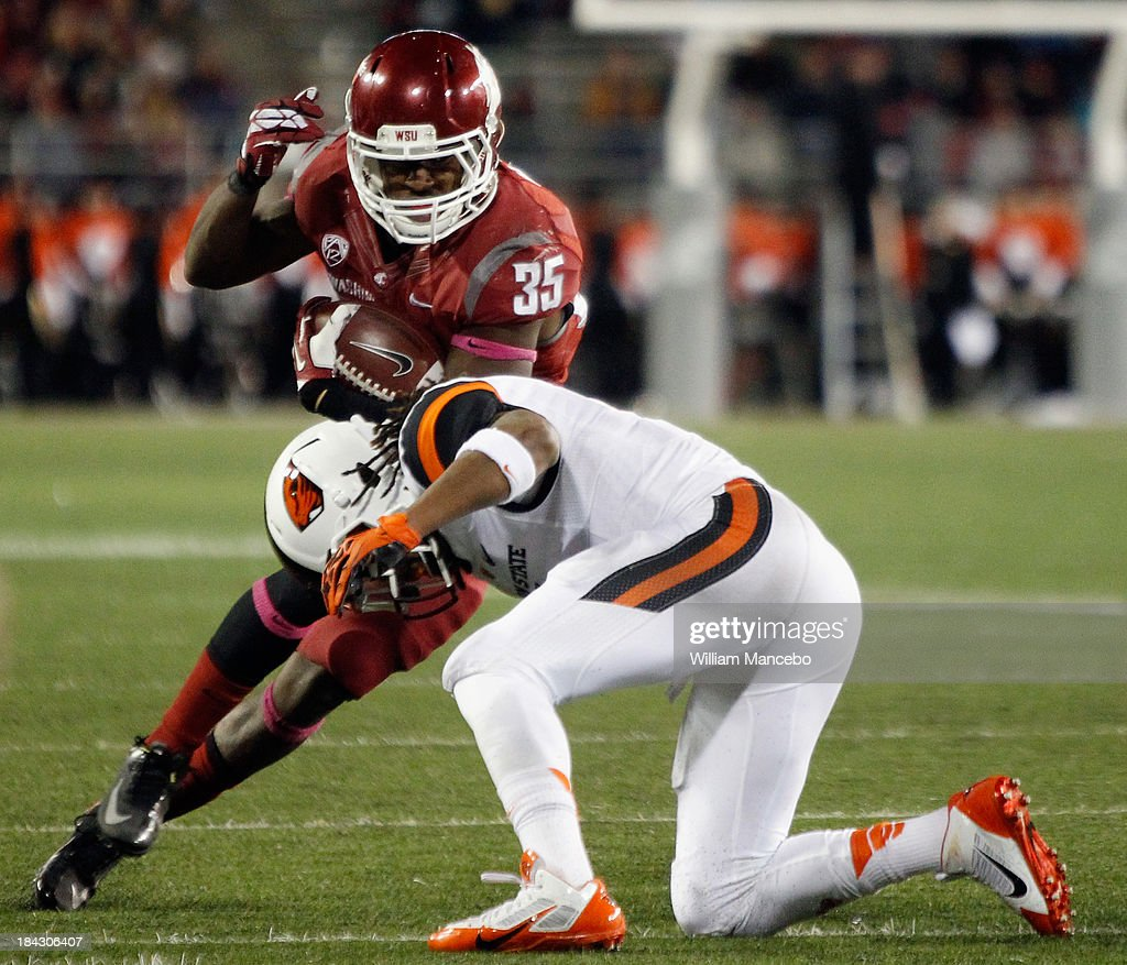 Marcus Mason #35 of the Washington State Cougars carries the ball against Steven Nelson #2 of the Oregon State Beavers during the game at Martin Stadium on October 12, 2013 in Pullman, Washington.