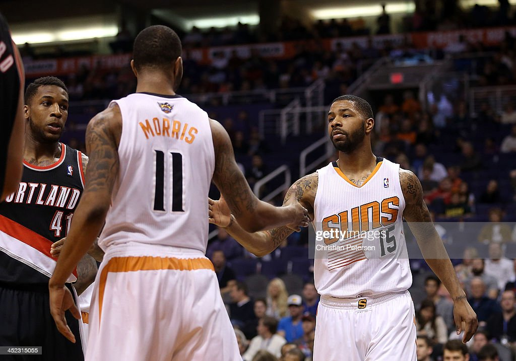 Marcus Morris #15 (R) of the Phoenix Suns high-fives Markieff Morris #11 after scoring against the Portland Trail Blazers during the second half of the NBA game at US Airways Center on November 27, 2013 in Phoenix, Arizona. The Suns defeated the Trail Blazers 120-106.