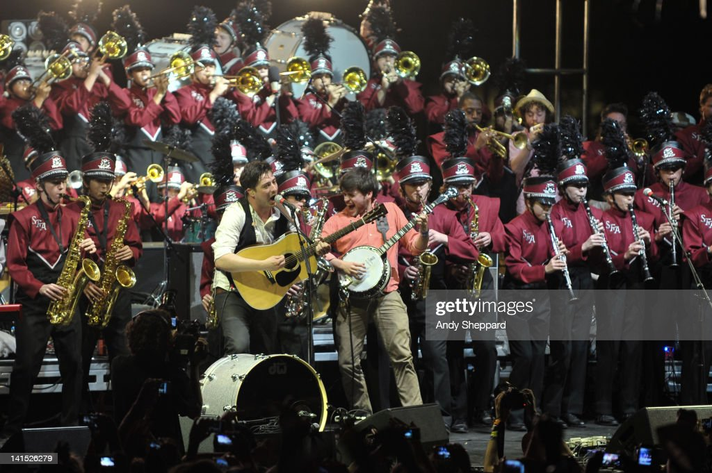 Marcus Mumford and Winston Marshall of Mumford Sons perform on stage with members of the Austin High School Marching Band at LBJ Lawn University of...