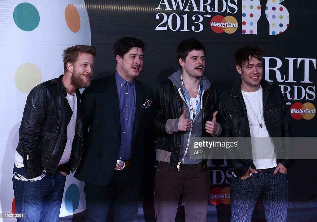Marcus Mumford, Ben Lovett, Winston Marshall, and Ted Dwane of British folk rock band Mumford and Sons pose on the red carpet arriving at the BRIT Awards 2013 in London on February 20, 2013.