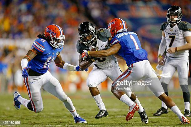 Marcus Murphy of the Missouri Tigers runs on a handoff from Maty Mauk as Neiron Ball and Vernon Hargreaves III of the Florida Gators defend during...