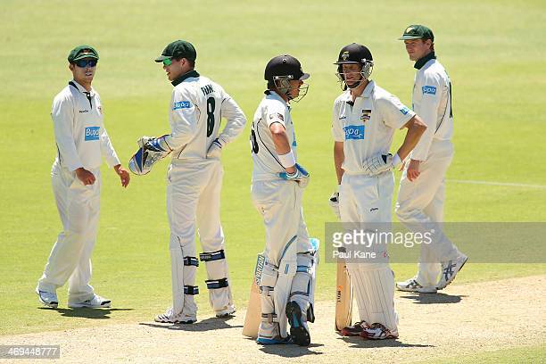 Marcus North and Adam Voges of the Warriors talk mid wicket as Jon Wells Tim Paine and George Bailey of the Tigers look on during day four of the...