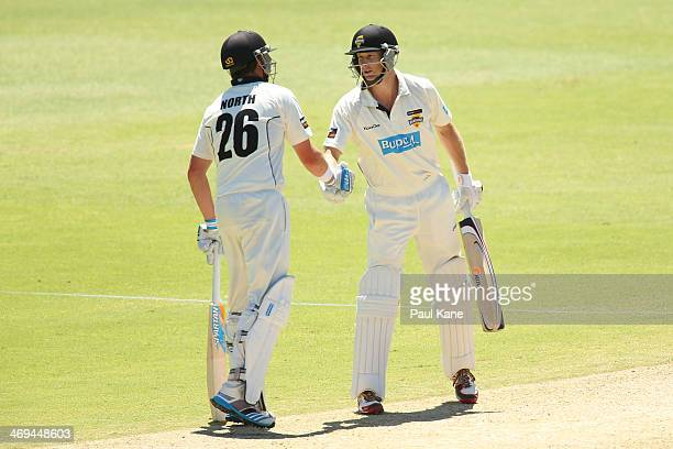 Marcus North of the Warriors congratulates Adam Voges after reaching his half century during day four of the Sheffield Shield match between the...