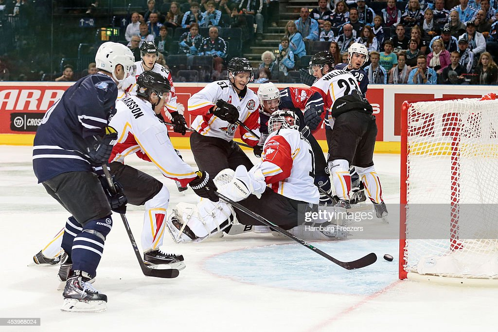 Marcus Oskarsson #03 of Lulea (L) saves a goal against Kevin Clark of #11 Hamburg Freezers during the Champions Hockey League group stage game between Hamburg Freezers and Lulea Hockey on August 22, 2014 in Hamburg, Germany.