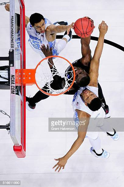 Marcus Paige and Kennedy Meeks of the North Carolina Tar Heels challenge a shot by Ben Bentil of the Providence Friars during the second round of the...