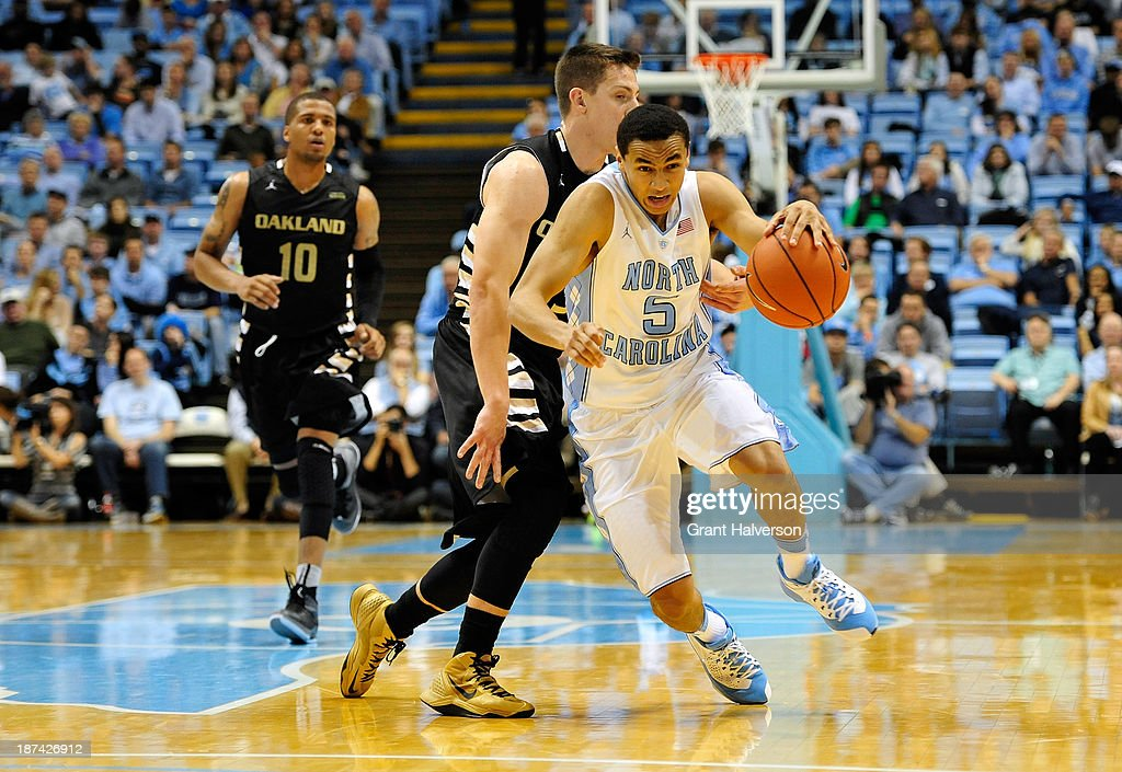 Marcus Paige #5 of the North Carolina Tar Heels dribbles past defender Travis Bader #3 of the Oakland Golden Grizzlies during play at the Dean Smith Center on November 8, 2013 in Chapel Hill, North Carolina. North Carolina won 84-61.