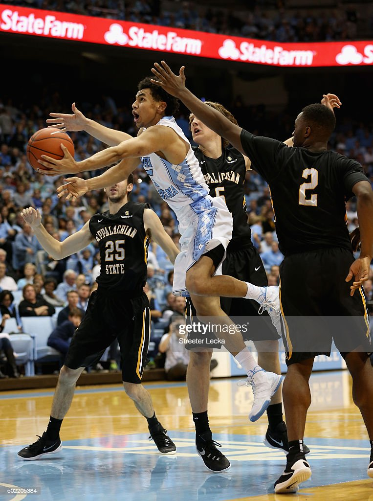 Marcus Paige of the North Carolina Tar Heels drives past teammates Griffin Kinney and Ronshad Shabazz of the Appalachian State Mountaineers during...