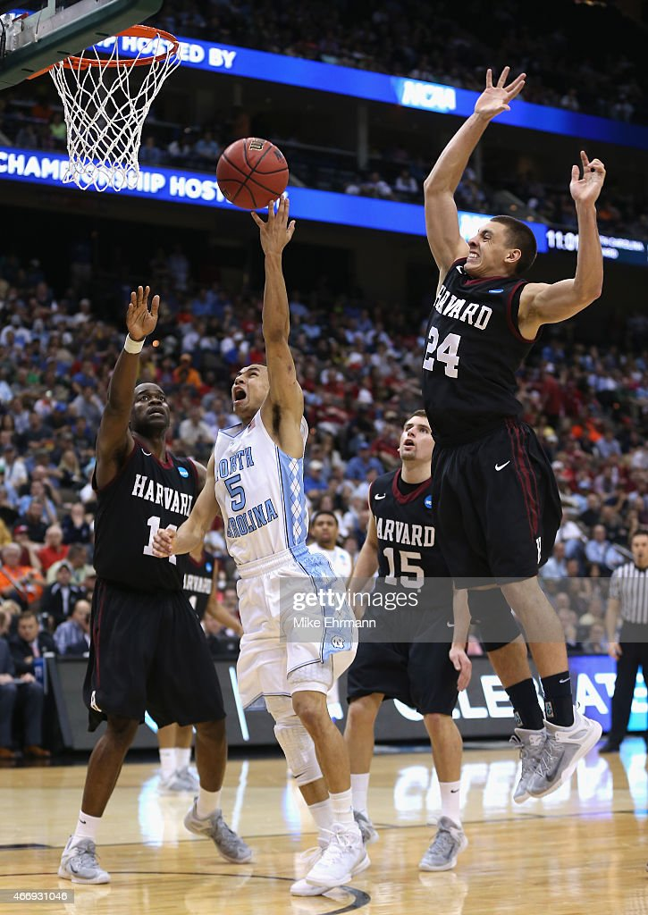 Marcus Paige of the North Carolina Tar Heels drives to the basket against teammates Steve MoundouMissi and Jonah Travis of the Harvard Crimson during...
