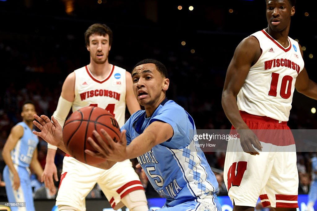 Marcus Paige of the North Carolina Tar Heels grabs the ball in front of Frank Kaminsky of the Wisconsin Badgers in the first half during the West...