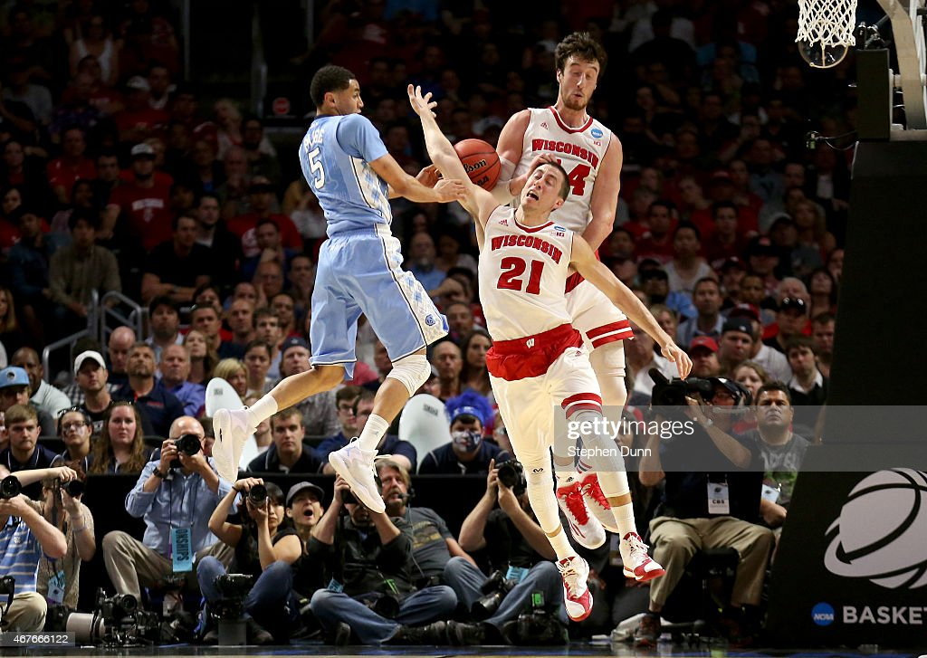 Marcus Paige of the North Carolina Tar Heels with the ball against Frank Kaminsky and Josh Gasser of the Wisconsin Badgers in the first half during...