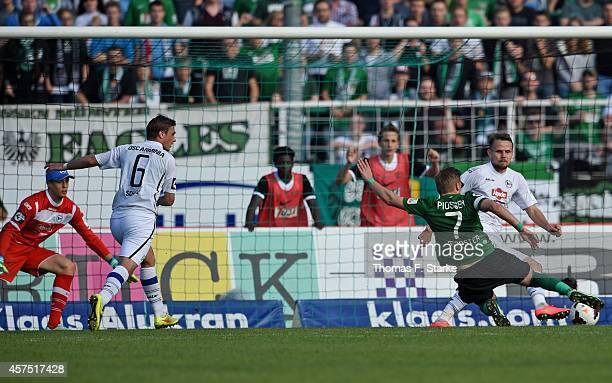 Marcus Piossek of Muenster scores against Sebastian Schuppan Tom Schuetz and Alexander Schwolow of Bielefeld during the Third League match between...