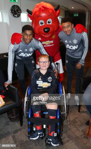 Marcus Rashford and Jesse Lingard of Manchester United pose with Tomos during a MU Foundation Dream Day at Aon Training Complex on October 20 2017 in...