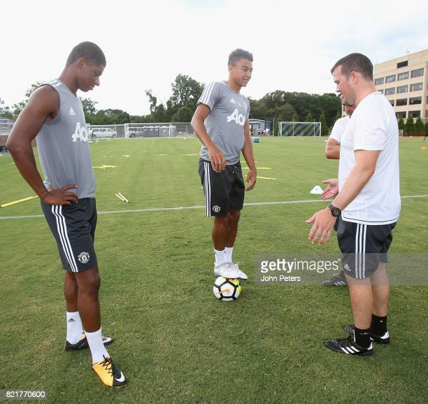 Marcus Rashford and Jesse Lingard of Manchester United talk to masseur Rod Thornley during a first team training session as part of their preseason...