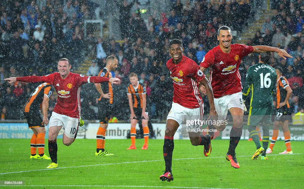 Marcus Rashford of Manchester United (C) celebrates scoring his sides first goal with his team mates Wayne Rooney of Manchester United (L) and Zlatan Ibrahimovic of Manchester United (R) during the Premier League match between Hull City and Manchester United at KCOM Stadium on August 27, 2016 in Hull, England.