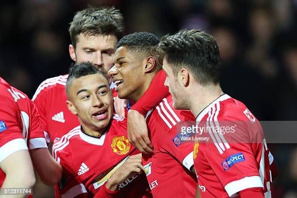Marcus Rashford of Manchester United celebrates scoring his team's third goal with his team mates during the UEFA Europa League Round of 32 second...