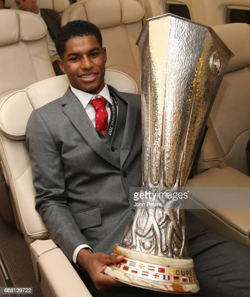 Marcus Rashford of Manchester United celebrates with the Europa League trophy on the plane home after the UEFA Europa League Final match between...