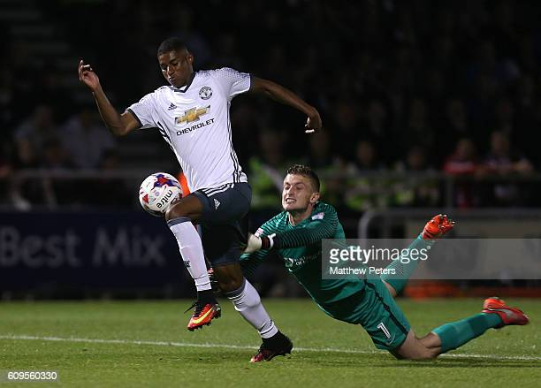 Marcus Rashford of Manchester United goes past Adam Smith of Northampton to score his team's third goal during the EFL Cup Third Round match between...