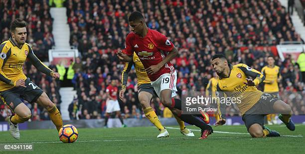 Marcus Rashford of Manchester United in action with Carl Jenkinson and Mohamed Elneny of Arsenal during the Premier League match between Manchester...