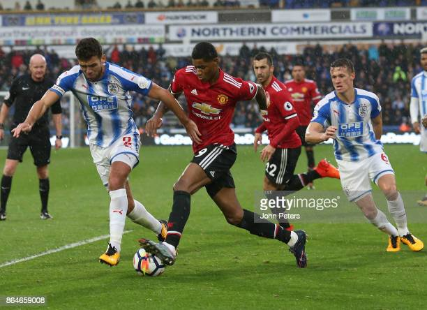 Marcus Rashford of Manchester United in action with Tommy Smith of Huddersfield Town during the Premier League match between Huddersfield Town and...