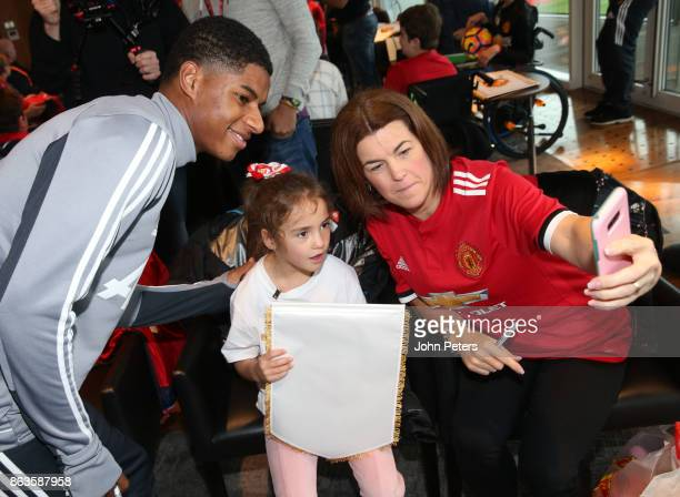 Marcus Rashford of Manchester United poses with Alice during a MU Foundation Dream Day at Aon Training Complex on October 20 2017 in Manchester...