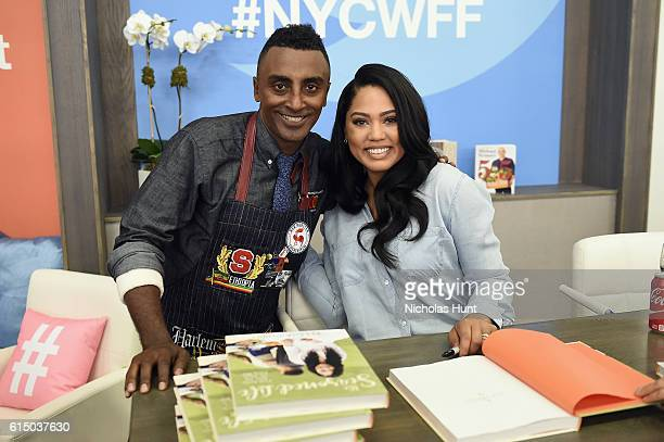 Marcus Samuelsson and Ayesha Curry pose at a cookbook signing during the Grand Tasting presented by ShopRite featuring Samsung culinary...