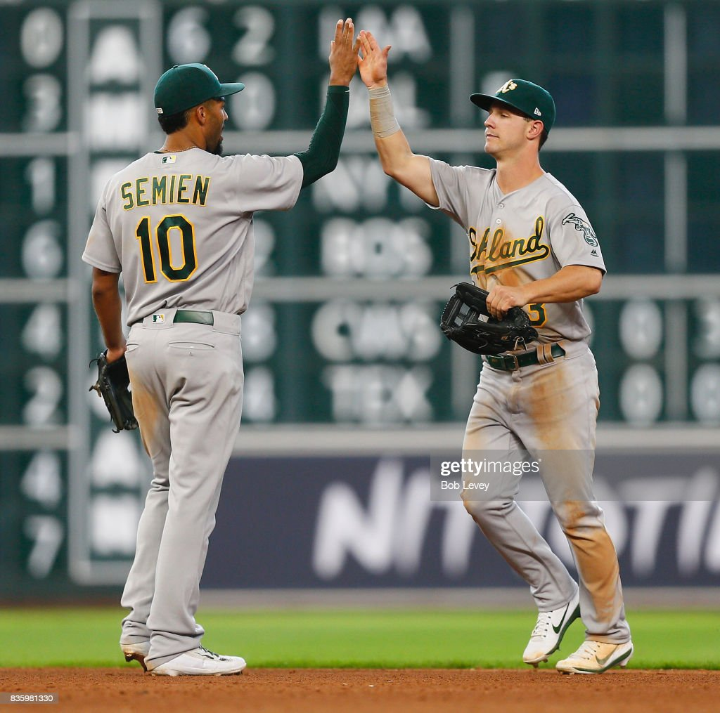 Marcus Semien #10 of the Oakland Athletics high fives Boog Powell #3 after the final out against the Houston Astros at Minute Maid Park on August 20, 2017 in Houston, Texas.